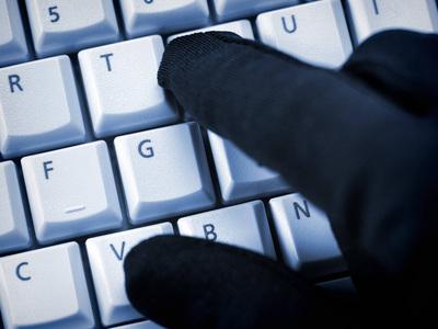Schwarze Hand auf Computertastatur Datenklau